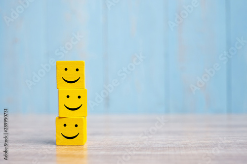 Obraz smile face on yellow wood cube. Service rating, ranking, customer review, satisfaction and emotion concept. - fototapety do salonu