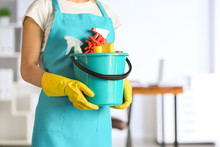 Female Janitor With Set Of Cleaning Supplies In Office
