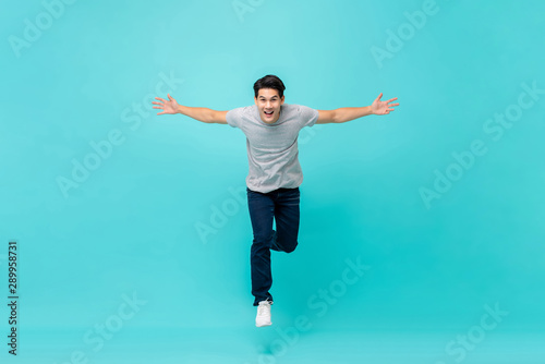 Fényképezés  Young cheerful energetic handsome Asian man jumping