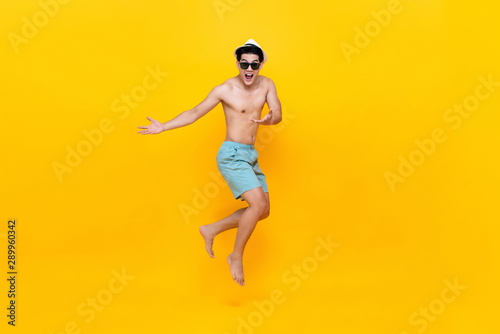 Fotografia  Amazed shirtless handsome Asian tourist man jumping