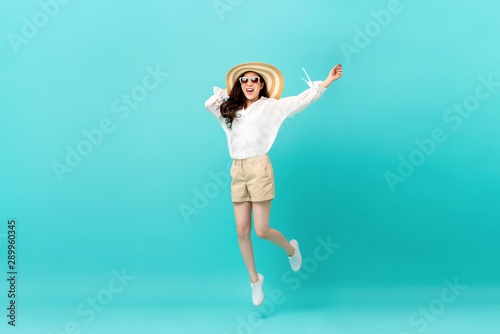 Studio shot of happy energetic asian woman wearing casual clothes jumping
