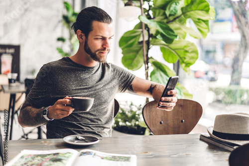 Handsome bearded hipster man use smartphone with coffee at table in cafe Fototapete