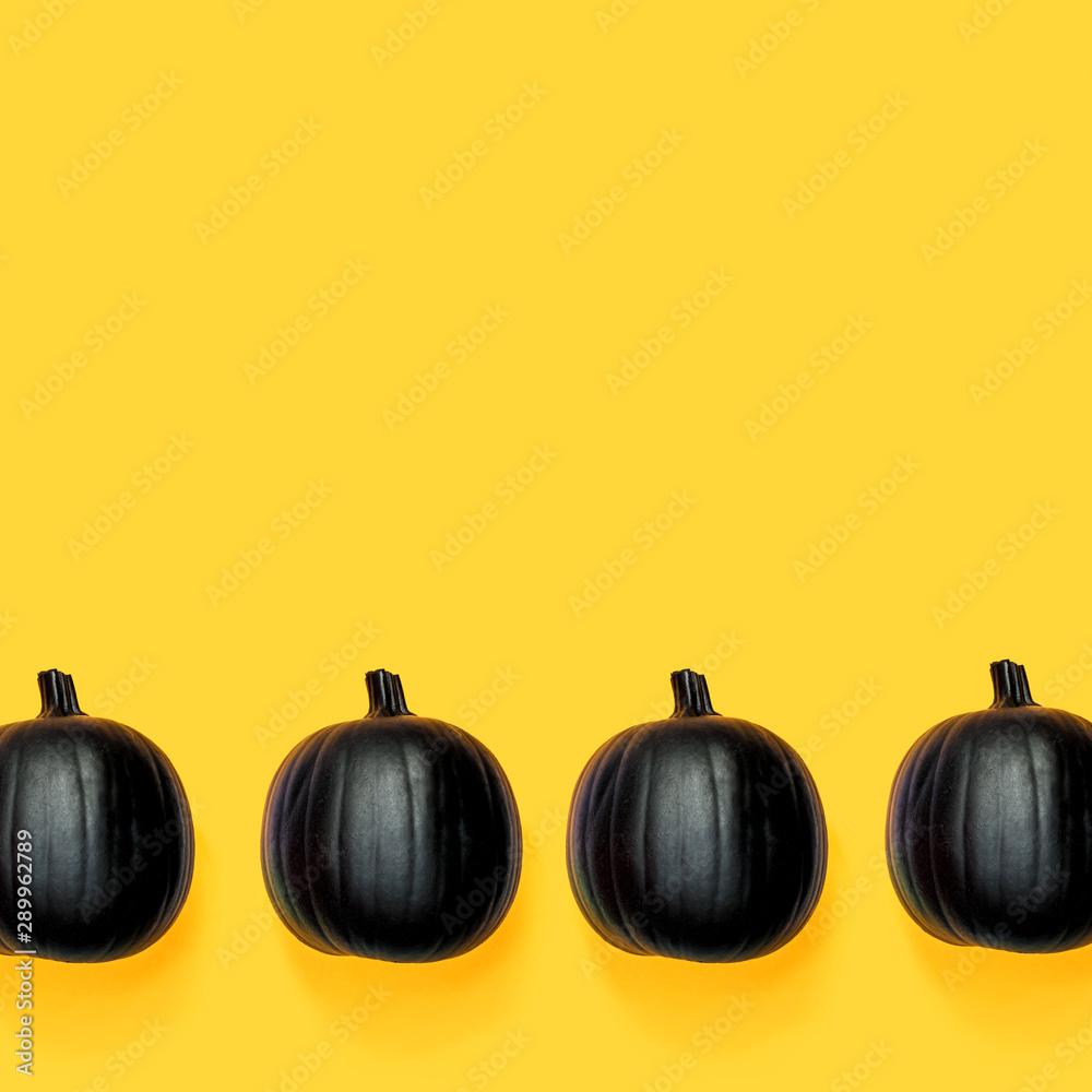 Fototapeta Black colored pumpkins on a bright yellow background
