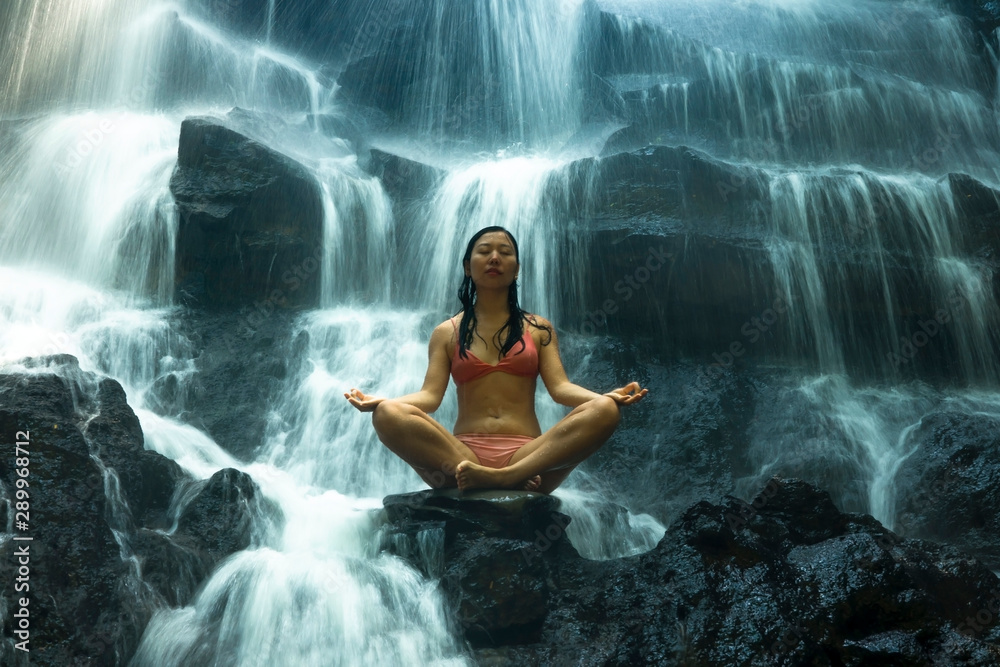 Fototapeta natural portrait of young beautiful and happy Asian Chinese woman in bikini enjoying nature at tropical paradise waterfall with magical feeling in soul inspiration