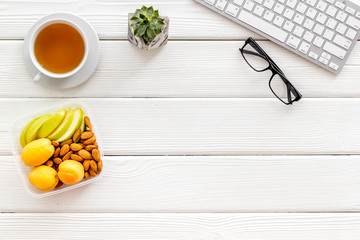 Food container with healthy food on office desk with keyboard and tea on white wooden background top view copyspace