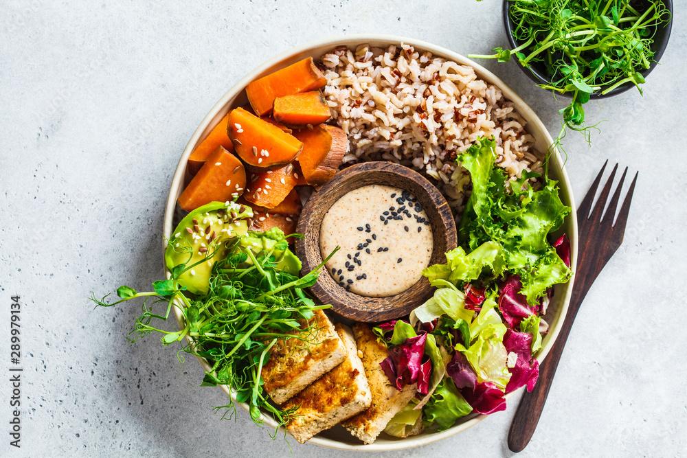 Fototapety, obrazy: Buddha bowl with tofu, avocado, rice, seedlings, sweet potato and tahini dressing.