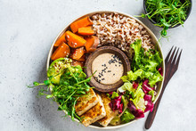 Buddha Bowl With Tofu, Avocado, Rice, Seedlings, Sweet Potato And Tahini Dressing.