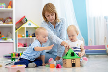 Nursery Babies And Kindergarten Teacher Playing With Educational Toys
