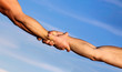 Helping hand concept and international day of peace, support. Two hands, helping arm of a friend, teamwork. Hands of on blue sky background. Helping hands concept, support. Close up help arm