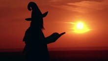 Woman In Halloween Costume Sorceress Turns Pages Of A Magic Book On The Hill Sky With Yellow Sun