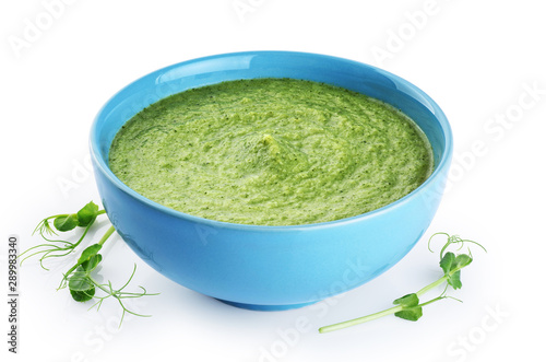 Bowl of green cream soup with pea sprouts, broccoli, kale and spinach  isolated on white background.