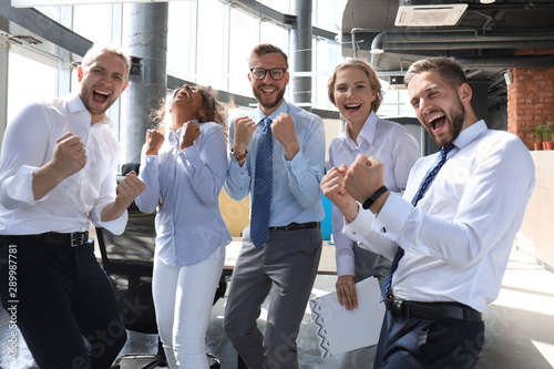 Fotografía  Five happy modern business people are keeping arms raised and expressing joyful