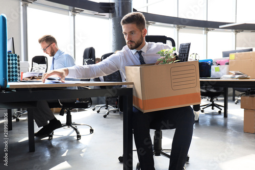 Sad dismissed worker are taking his office supplies with him from office Fototapet