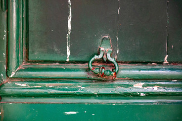 Old grungy surface of antique door with vintage damaged rusty door knocker closeup on background of dirty painted wooden door frames with peeling green paint. Architectural backdrop