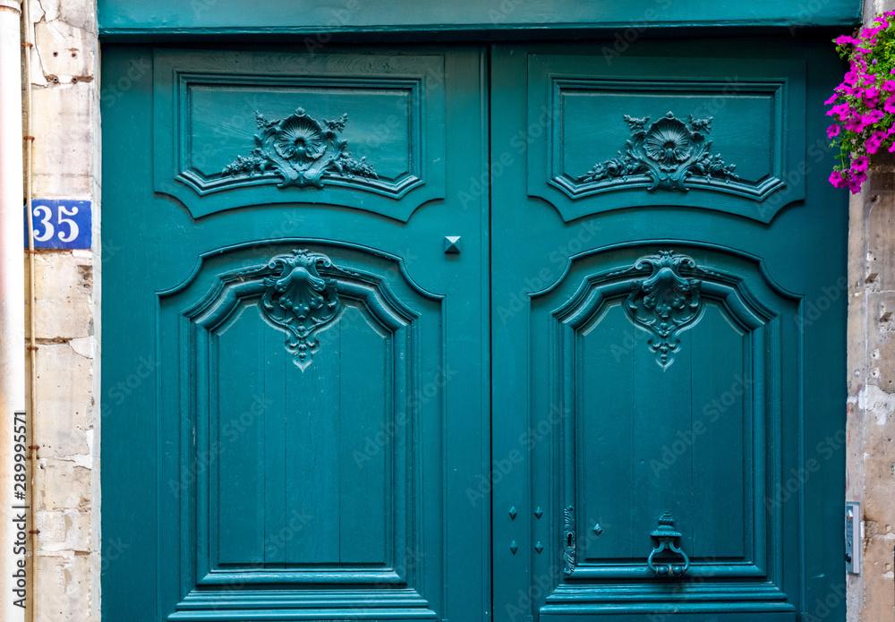 Fototapeta Old wooden door. Baroque style sculptural details of gorgeous antique wooden door painted in beautiful aquatic blue color. Top part of vintage double door of old stone building in Paris France.
