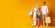 Parents And Daughter Carrying Colorful Shopping Bags In Studio, Panorama