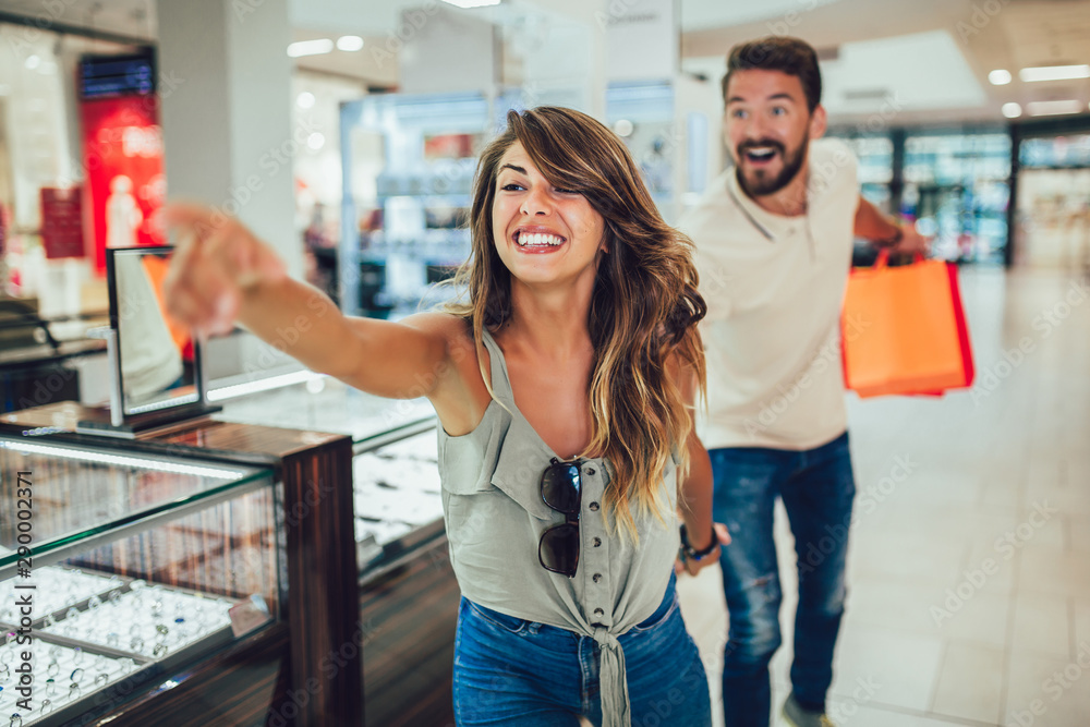 Fototapeta Couple having fun in shopping mall while doing shopping together