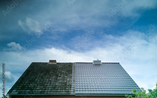 Obraz A half cleaned house roof shows the before and after effect of a roof cleaning. - fototapety do salonu