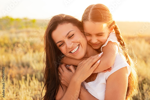 Daughter hugging mother in nature Wallpaper Mural