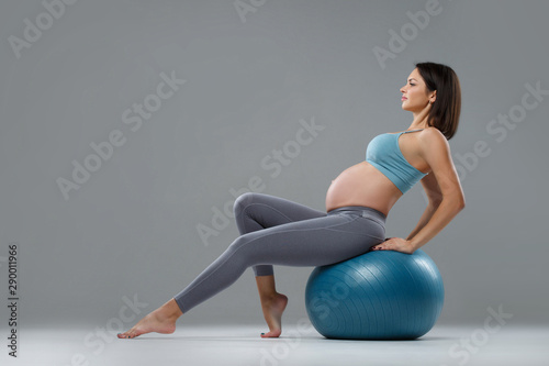 Fototapeta  Slender athletic pregnant girl is engaged in fitness on a ball Isolated on a gray background