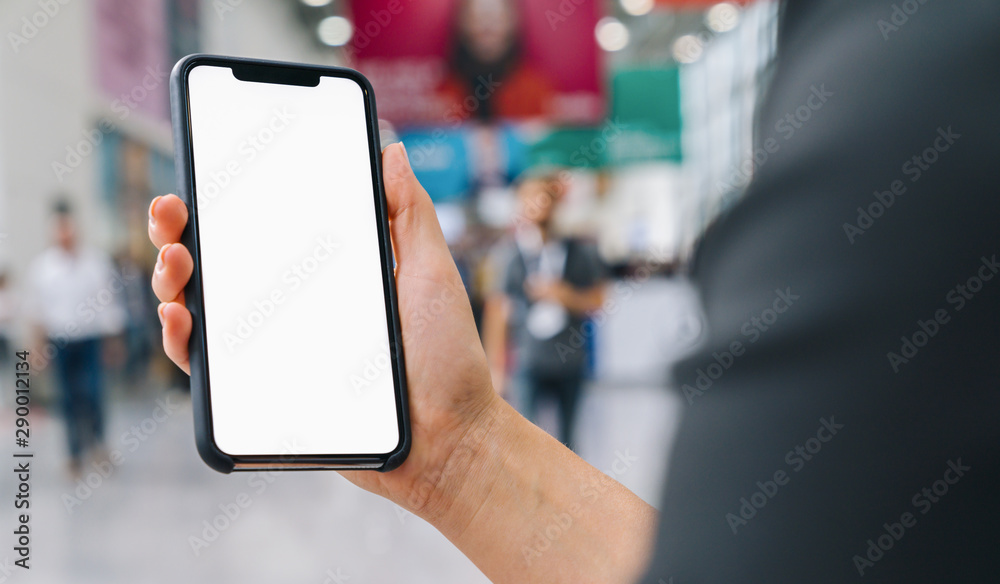 Fototapeta Female hand holding black cellphone with white screen at a trade fair, copyspace for your individual text.