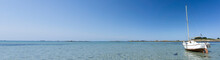 Very Wide Panorama Ocean Coast And Beach Landscape With Small Sailboat Under A Blue Sky