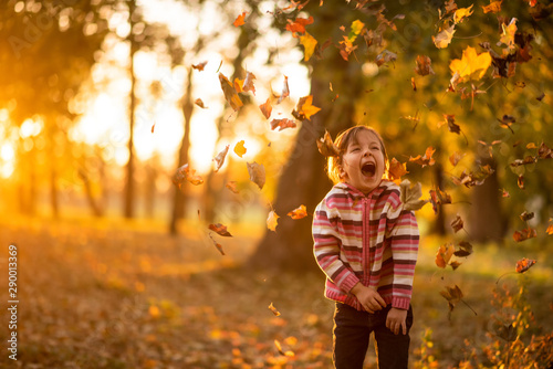 Fotografia  Cute little girl playing with leaves falling on her