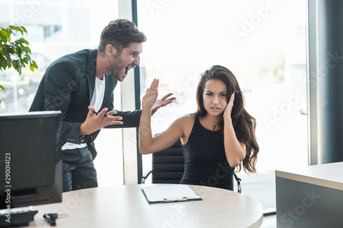 strict boss man swearing at upset tired employee woman for bad work at the workp Fototapet