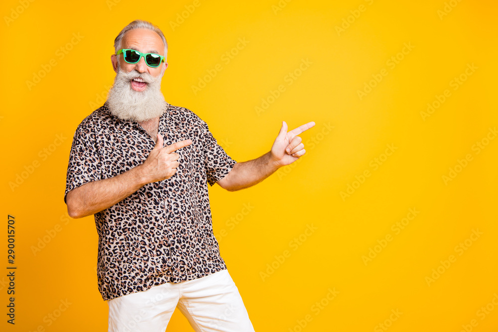 Fototapeta Portrait of crazy funny funky old bearded man with eyeglasses eyewear point at copyspace recommend sales discounts wear leopard print shirt isolated over yellow background