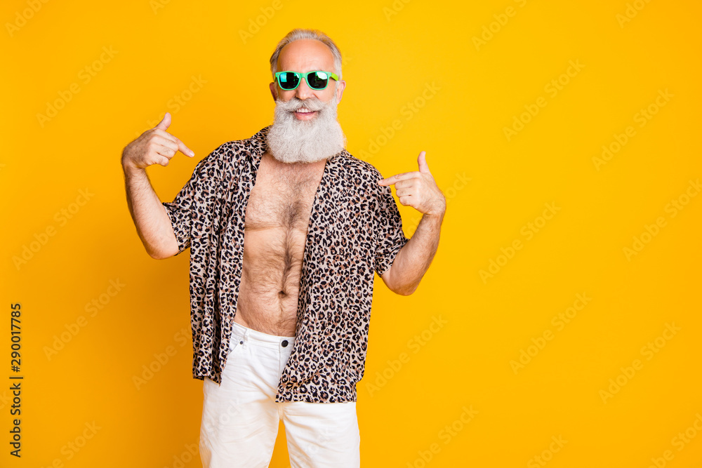 Fototapeta Photo of cheerful nice old man pointing at himself to show you his handsomeness while isolated with yellow background