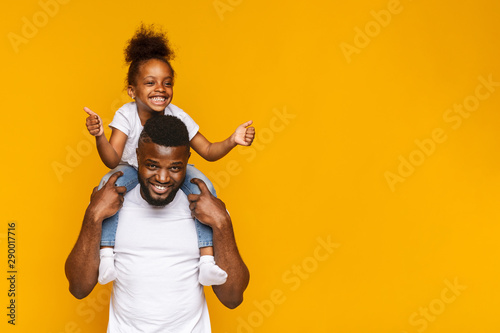 Adorable little african girl gesturing thumbs up on daddy's shoulders Fototapet