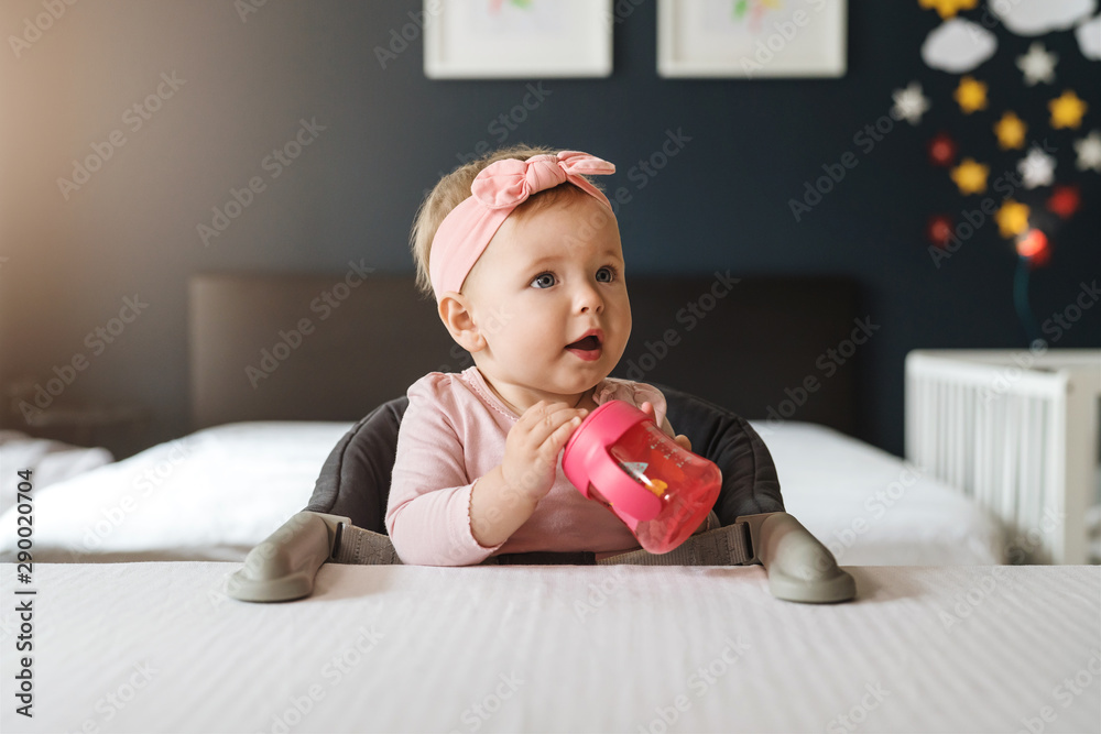 Fototapety, obrazy: Nine-month-old smiling baby girl in pink bandage sits at white table in highchair and drinks water from baby's cup.
