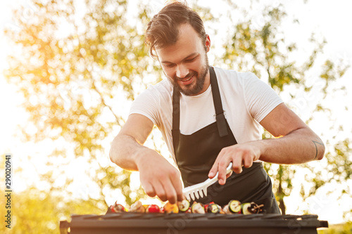 Fotomural Smiling chef with tongs preparing skewers on grill