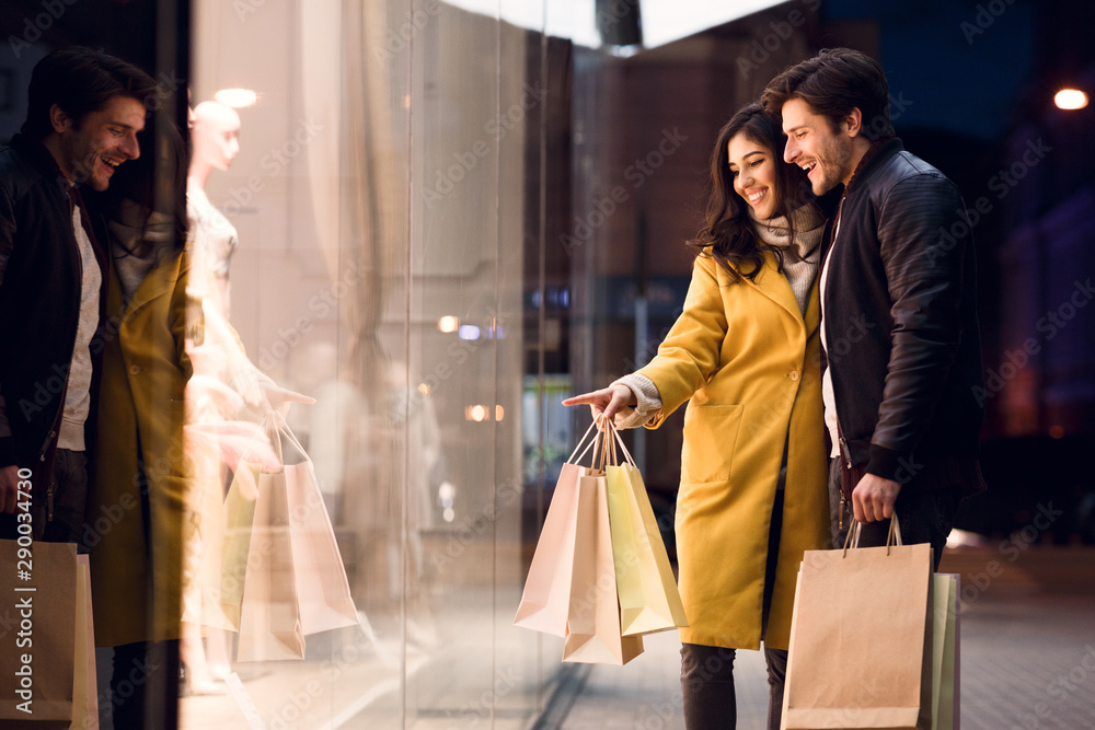 Fototapety, obrazy: Window shopping. Couple looking at fashion store's showcase