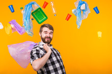 Environmental Pollution, Plastic Recycling Problem And Waste Disposal Concept - Funny Man Holding Garbage Bag On Yellow Background.