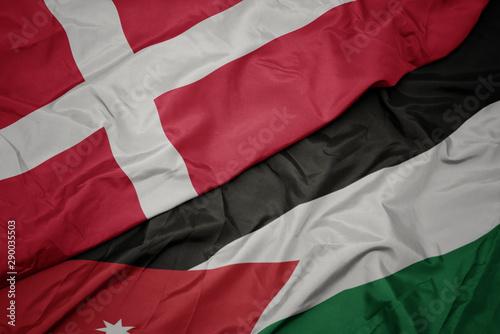 Photo  waving colorful flag of jordan and national flag of denmark.