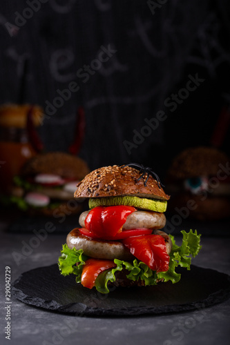 Homemade burger monsters for Halloween celebration on dark background. Halloween food and decoration.