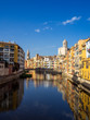 Girona's tipical skyline cityscape over the Onyar River with colourful river houses on a blue sunny sky, Church of Sant Feliu Cathedral landmark on background
