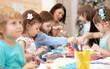 canvas print picture Group of children on hand arts lesson in kindergarten. Teacher helps kids hands working. Preschool students activities in class