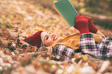Young Woman Lying And Reading Her Favorite Book On  O Autumn Meadow