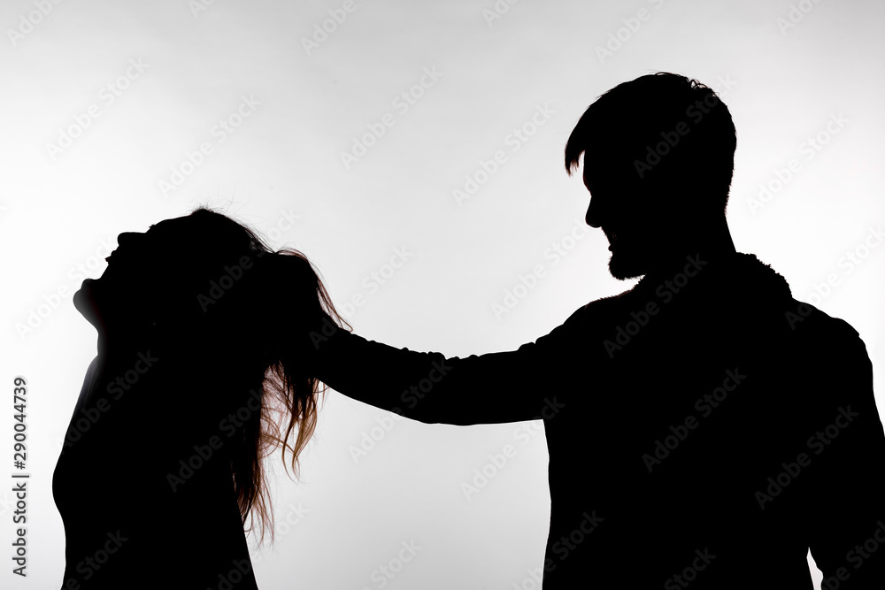 Fototapeta Aggression and abuse concept - man and woman expressing domestic violence in studio silhouette isolated on white background.