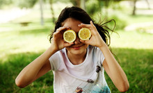 Happy 12 Year Old Girl Smiling And Holding Lemon Slices