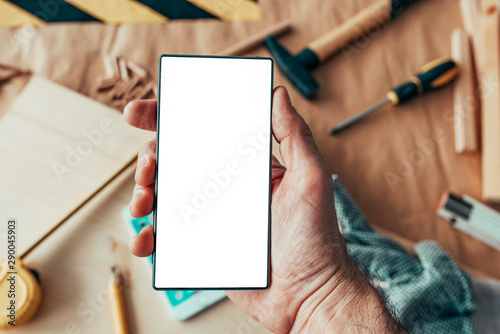 Fotomural  Handyman maintenance worker holding smartphone with blank mock up screen