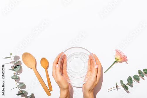 Fototapeta View from above female hands holding empty glass bowl obraz