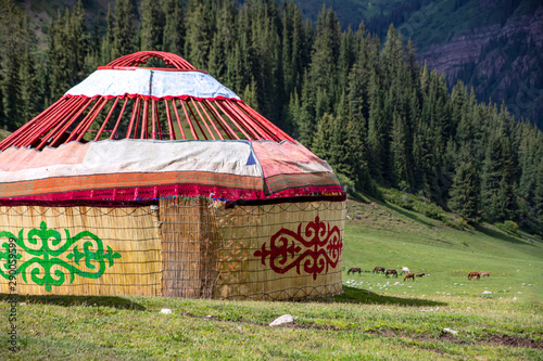 Obraz na plátně Almost ready-made Kyrgyz traditional yurt house on the background of mountains covered with coniferous forest