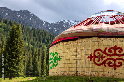 Fototapeta Almost ready-made Kyrgyz traditional yurt house on the background of mountains covered with coniferous forest