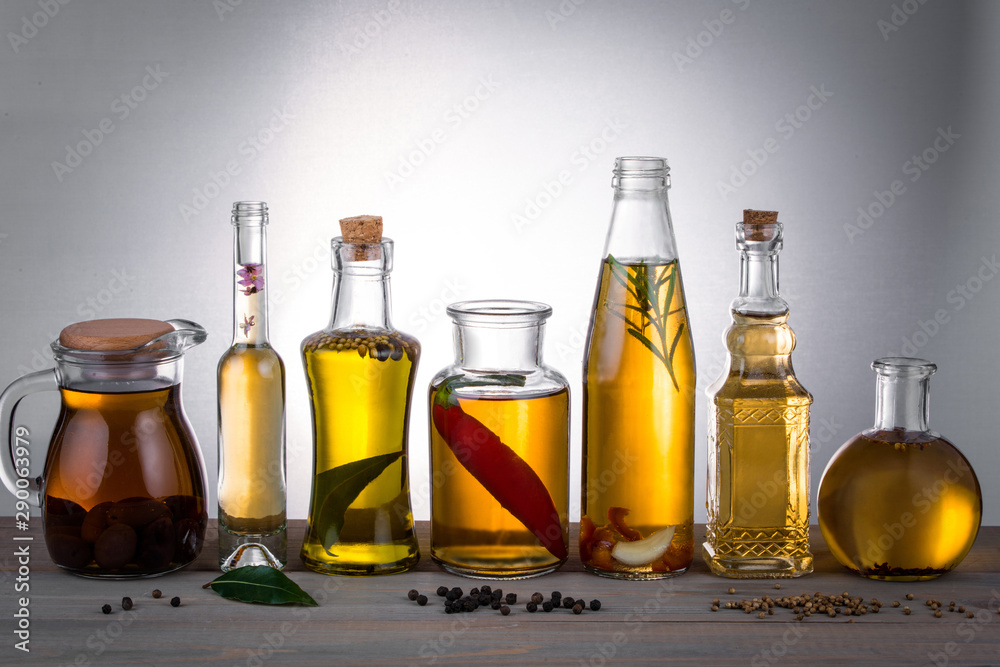 Fototapety, obrazy: Oil in bottles with butter, olive oil with herbs and spices on the table.