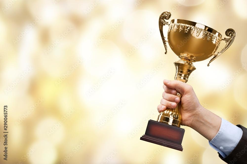 Fototapety, obrazy: Hands holding golden trophy on light background