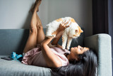 woman play with exotic shorthair cat on sofa