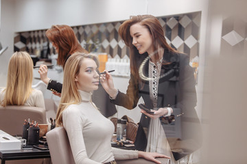 Makeup artist woman applying powder on the face of a beautiful young blonde woman sitting in a chair in a beauty salon. Concept of grooming women